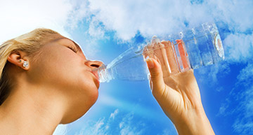 Woman drinking a bottle of water | Water Softeners / Conditioners